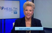 Joan Lunden smiling with TV in the background